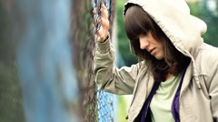 Sad beautiful woman by chain-link fence, outdoors HD - stock footage