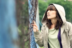 Sad beautiful woman by chain-link fence, outdoors NTSC Stock Footage
