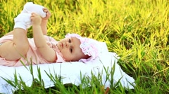 Baby lying on the grass and look at camera Stock Footage