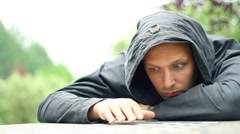 Sad man in the hood in the park Stock Footage