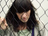 Stock Video Footage of Portrait of sad woman behind chain-link fence, outdoors