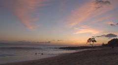 Hawaiian Beach Sunset kids body surfing clouds and tree Stock Footage