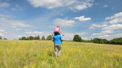 Girl ride the father in the summer field - stock footage