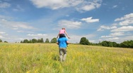 Girl ride the father in the summer field Stock Footage
