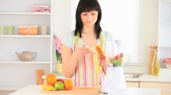 Dark-haired woman preparing a smoothie Stock Footage