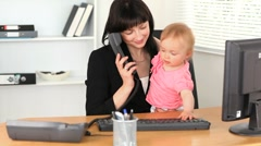Working mother at the office with her baby Stock Footage