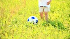 Little football player kicks the ball Stock Footage