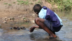African Boy in School Clothes Drinks from Polluted Stream (HD) Stock Footage