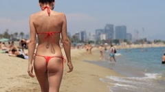Sexy girl in thong bikini walking on the beach, steadicam shot, slow motion Stock Footage
