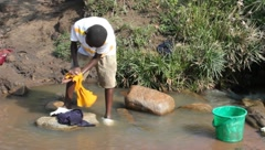 African Boy Washing Clothes in Polluted Stream (HD) Stock Footage