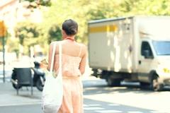 Attractive woman crossing city street, steadicam shot NTSC Stock Footage
