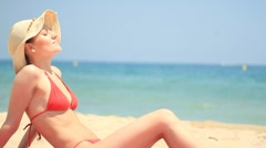 Attractive woman in summer hat sunbathing on the beach HD Stock Footage