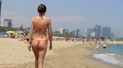Sexy woman in red thong bikini walking on beach, slow motion, steadicam HD Stock Footage