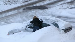 Woman try to dig out her car after snow storm Stock Footage