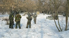 Children and adults play paintball in winter Stock Footage