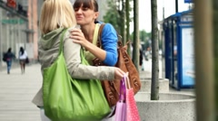 Two female friends meeting after shopping in the city HD Stock Footage