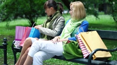 Two female friends with checking shopping bags on park bench HD - stock footage