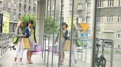 Two female friends with dhopping bags looking at shop window HD Stock Footage