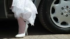 Feet of  bride in  wedding dress leaving of  car Stock Footage