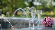 Bridal bouquet and two glasses of champagne near fountain Stock Footage