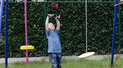 Little boy having good time on swing in the yard - stock footage