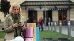 Attractive woman with shopping bags sending sms in the city HD Stock Footage