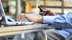 Businessman talking on mobile phone and working on laptop, steadicam shot HD Stock Footage