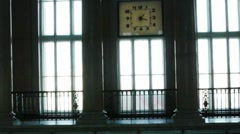 Young female silhouete in front of large window under clock Stock Footage