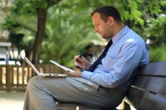 Businessman working with laptop and documents in the city, steadicam shot NTSC - stock footage