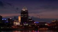 Helicopter flies across Cincinnati skyline seen at night Stock Footage