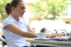 Businesswoman working on laptop in restaurant, urban scene, steadicam NTSC Stock Footage