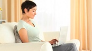 Brunette woman typing on a laptop Stock Footage
