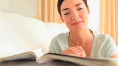 Brunette woman reading a magazine Stock Footage