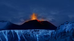 Volcano in Iceland rages into the late night sky above fields of glaciers. Stock Footage