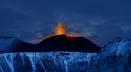 Stock Video Footage of Volcano in Iceland rages into the late night sky above fields of glaciers.
