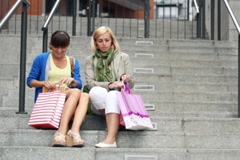 Two female friends meet in the city and sharing their new purchases Stock Footage