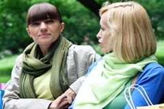 Two female friends sitting on a bench outdoor and chatting each other Stock Footage