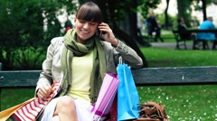 Young  woman sitting on bench after shopping and talking on the phone Stock Footage