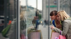 Two female friends looking at shop window Stock Footage