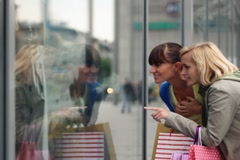 Two female friends looking at shop window - stock footage