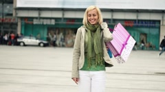 Young attractive woman with shopping bags in the city Stock Footage