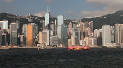 Ferry moving across Hong Kong Harbour with City Skyline, China, Asia - stock footage