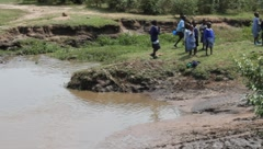 Land Cruiser Passes through Muddy Stream as Children Stand Aside  (HD) Stock Footage