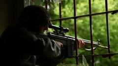 Sniper looking out of window - stock footage