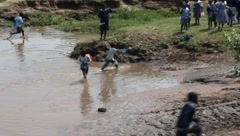 African Children in Muddy Stream and Vehicles Passes  (HD) Stock Footage