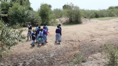 African School Children Contemplate Crossing Muddy Stream (HD) Stock Footage