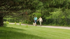 Senior couple walking dog at the park Stock Footage