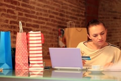 Woman with credit card overwhelmed by her shopping bills NTSC - stock footage