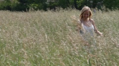Women walks through Field of Grass Stock Footage
