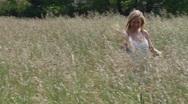 Women walks through Field of Grass Stock Footage